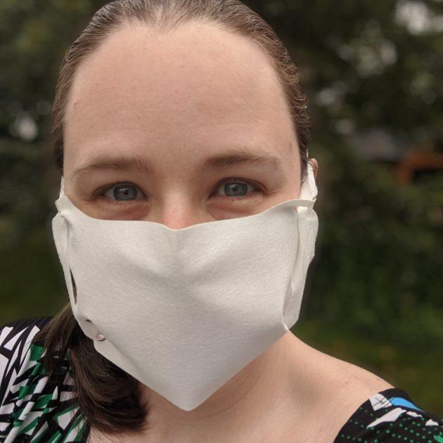 a woman wearing a white mask